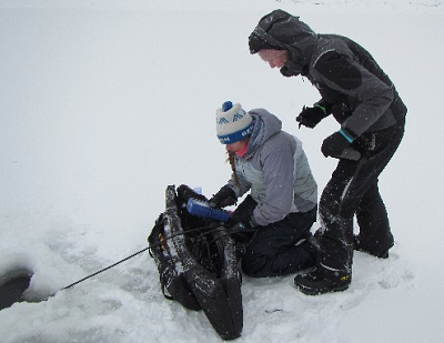 Department limnologist, Jana Tondu, (kneeling) performs water quality testing on the Athabasca River in January 2015