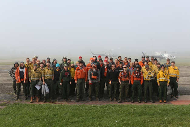 Wildland Firefighters from Alberta, Ontario and Idaho wait for smoke to lift before starting their day on the fireline – June, 2015